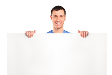Cheerful man standing behind a blank panel