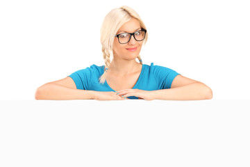 Blond girl with glasses posing behind a panel