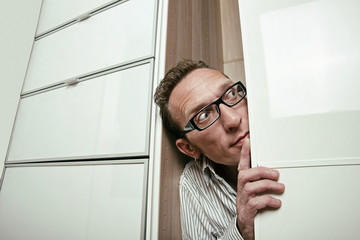 Frightened man peep out white wardrobe  Copy space right