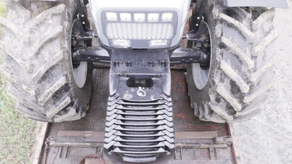 gray tractor pulls into the platform carriage background of road