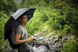 Young man in lush, green mountains holding an umbrella