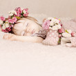 Cute baby girl sleep with flowers on vintage background
