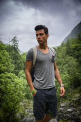 Handsome athletic young man with backpack in mountains