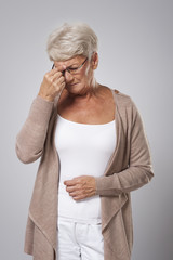 Senior woman suffering from strong headache