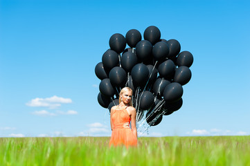 attractive woman with black balloons on the field