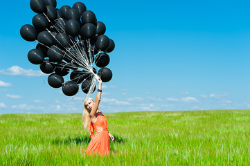 beautiful woman in a dress and black balloons