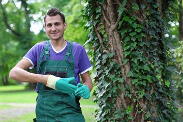 freundlicher Gärtner neben einem Baum