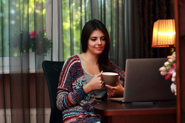 Beautiful woman holding cup of coffee and looking at laptop