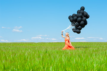 woman with black balloons walking on the green field