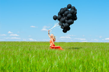 woman with black balloons running on the green field wheat