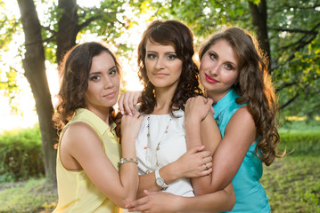 Three young beautiful ladies posing during walk in the city park
