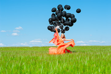 fashionable woman in the orange dress with black balloons