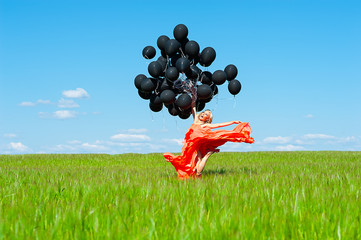 beautiful woman jumping with black balloons in hands