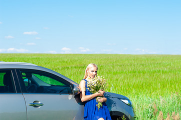 beautiful woman with daisies in hands standing near the car