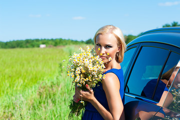 woman with daisies in hands standing near the car