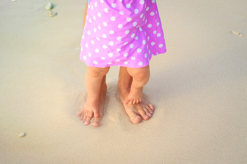 father and little daughter feet on a tropical beach