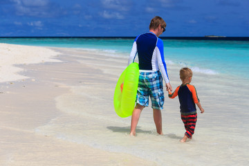 father and son go swimming at the beach