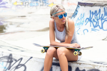 Teenage girl with skateboard sitting in skatepark