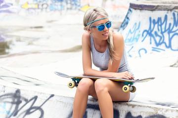 Teenage girl with skateboard sitting in skatepark