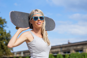 Young girl standing and holding skateboard behind her head