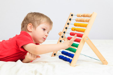 little boy playing with abacus