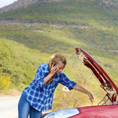 Young woman near broken car