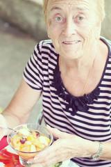 grand-mère mangeant une salade de fruit