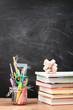 canvas print picture - School accessories on desktop with blank blackboard in the backg