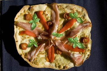 Pizza with tomatoes, pepper, ham and basil top view
