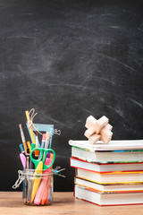 School accessories on desktop with blank blackboard in the backg