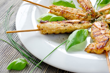 Grilled chicken kebab with herbs on a plate