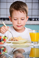 boy eating at the table, looking at the plate. vertical