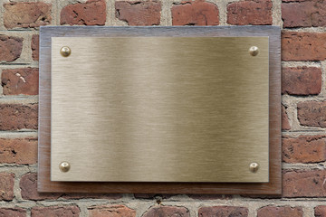 Brass or bronze metal plate on brick wall