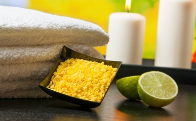 Spa massage border with towel stacked sea salt candles and lime