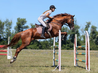 Teenage girl rider going over oxer
