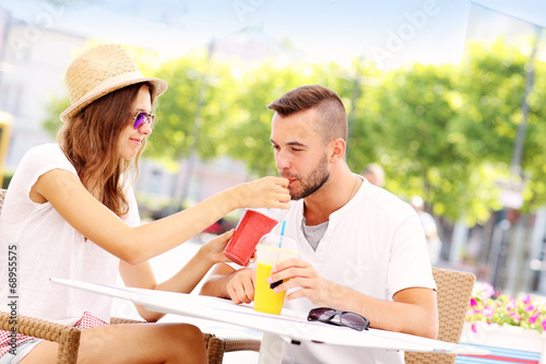 Happy couple drinking smoothies in an outside cafe - 68955575