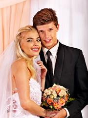 Wedding couple holding flower.