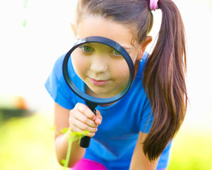 Little girl is looking through magnifier