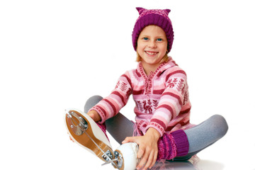 Young girl sitting on ice in skates