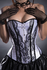 Close-up shot of a busty woman in elegant white corset