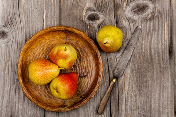 Birnen in einer Holzschale mit Messer