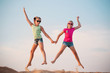 two girls jumping over blue sky