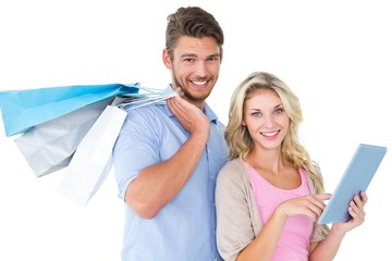 Attractive young couple holding shopping bags using tablet pc