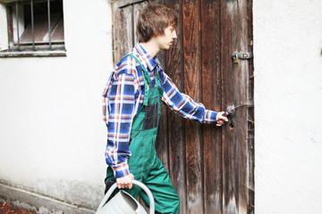 Gärtner mit Gießkanne betritt Geräteschuppen