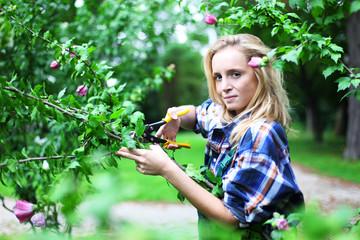 junge Gärtnerin schneidet Strauch