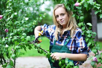junge Gärtnerin schneidet Äste