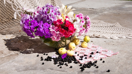 Bouquet of phloxes in a vase with apples and black berries