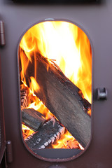 Fire-wood are burning in a stove with an opened door
