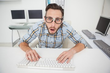 Puzzled nerdy businessman working on computer