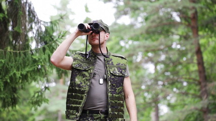 young soldier or hunter with binocular in forest